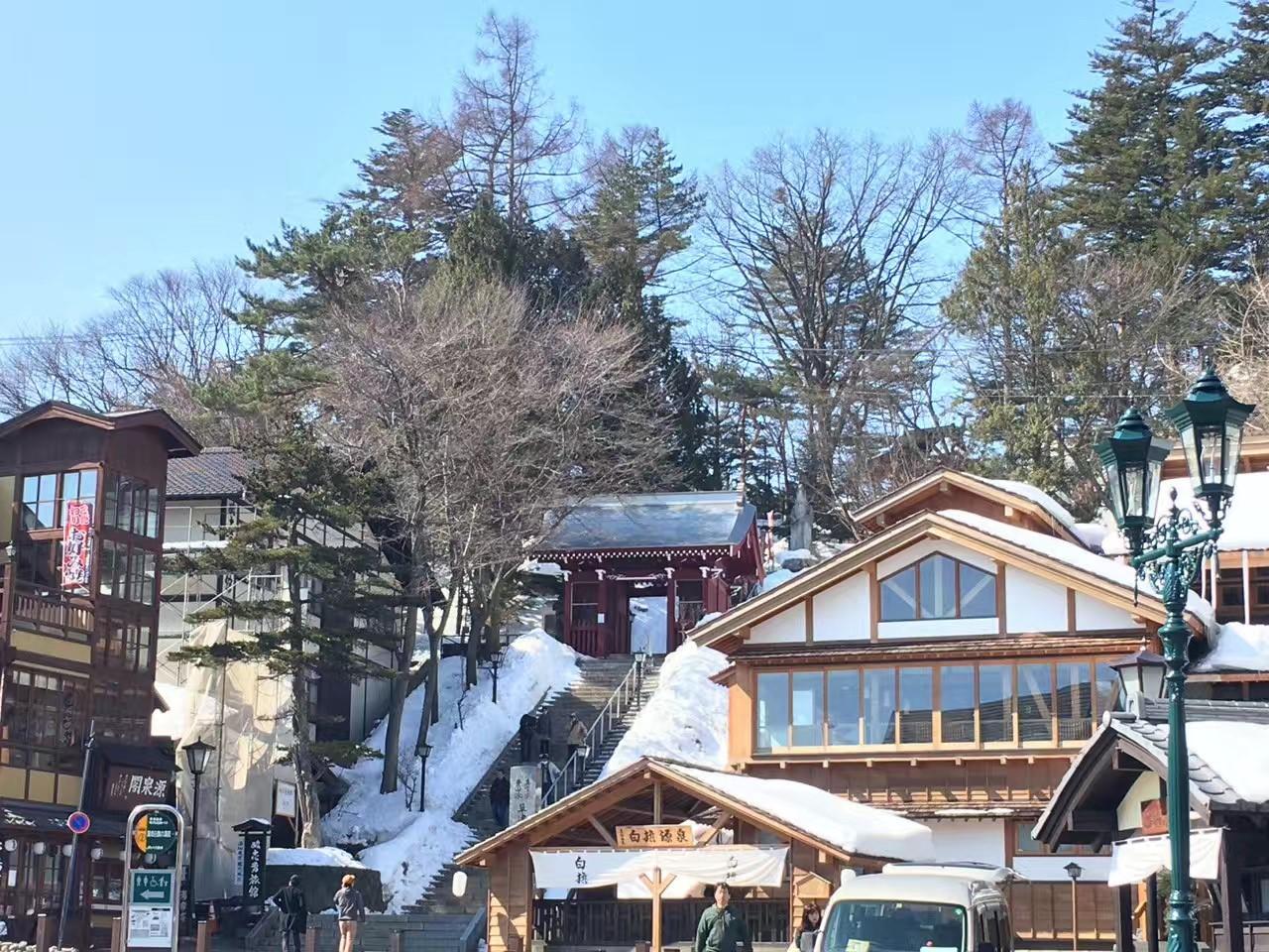 温泉の煙と青い空と白い雪のコントラスト